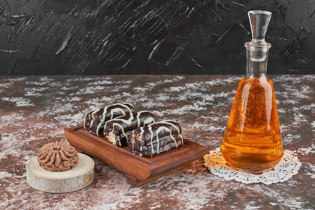 Brownies e uma garrafa de bebida em uma placa de madeira.