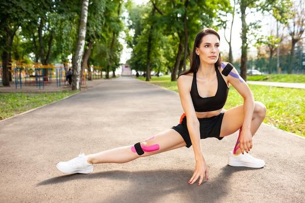 Bruette garota flexível com corpo perfeito se aquecendo ao ar livre