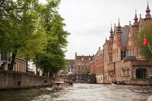 Bruges, bélgica, vista panorâmica com canal e ponte, barco, árvores e torre de igreja