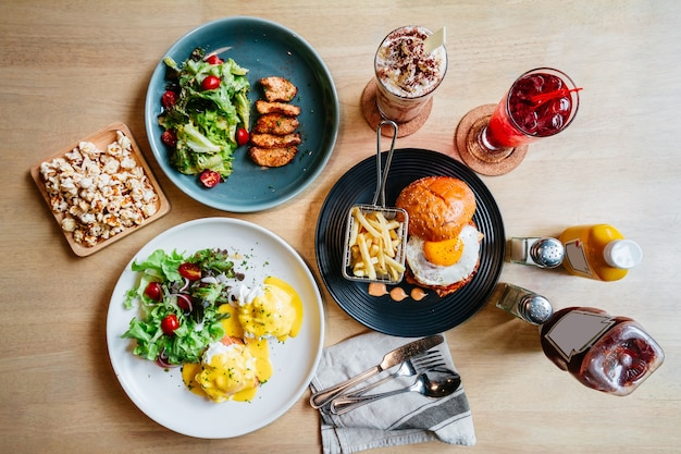 Brunch conjunto incluindo ovo benedict, frango grelhado e hambúrguer com ovo frito com pipoca
