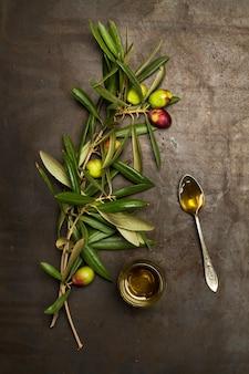 Brunch de azeitonas com folhas e azeite em um copo sobre uma mesa de metal enferrujada