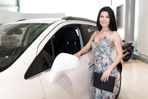 Brunet elegante bonito olha para seu novo carro no showroom da concessionária