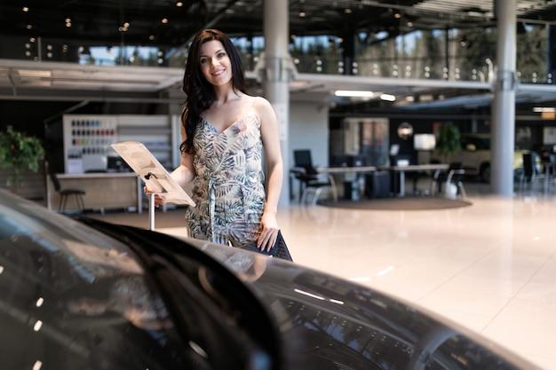 Brunet fascinante que verifica a descrição de carro novo no centro de negócio