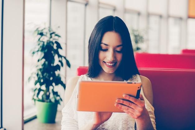 Brunette mulher que verific seu tablet