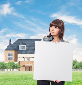 Brunette mulher segurando uma placa em branco com fundo da casa