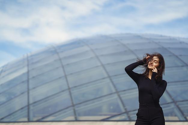 Brunetter garota ao lado de um edifício moderno