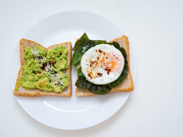Bruschetta apetitoso com ovo e abacate em uma placa. no sanduíche, a polpa de abacate