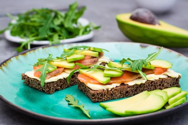 Bruschetta apetitoso com salmão, manteiga, abacate e rúcula em um prato