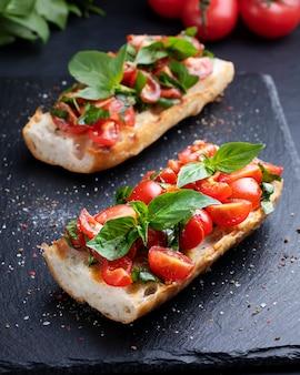Bruschetta caseira com tomate cereja e closeup de manjericão em uma placa de ardósia. cozinha italiana. antipasti. comida vegana