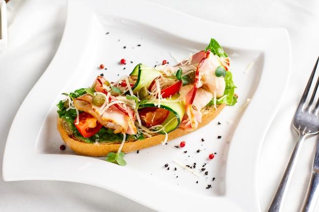 Bruschetta com bacon, legumes frescos e alcaparras na chapa branca