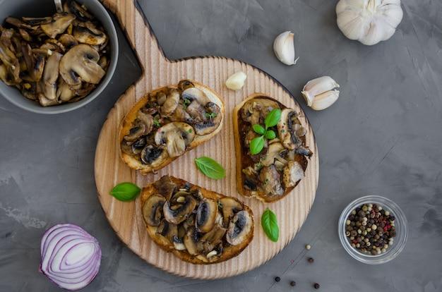 Bruschetta com cogumelos fritos com cebola, alho, tomilho e manjericão sobre uma tábua sobre um fundo escuro e concreto. orientação horizontal.