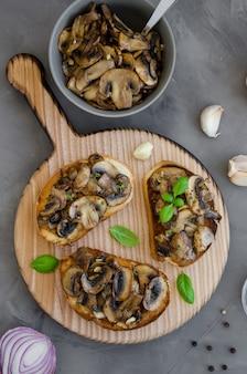 Bruschetta com cogumelos fritos com cebola, alho, tomilho e manjericão sobre uma tábua sobre um fundo escuro e concreto. orientação vertical.