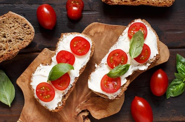 Bruschetta com cream cheese, tomate cereja e manjericão em uma mesa de madeira
