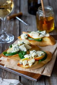Bruschetta com espinafre, pêra e queijo azul. vinho. comida vegetariana. alimentação saudável. veganismo. dieta.