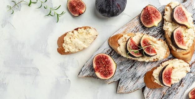 Bruschetta com figos e queijo de cabra, menu de receitas italianas. formato de banner longo. vista do topo
