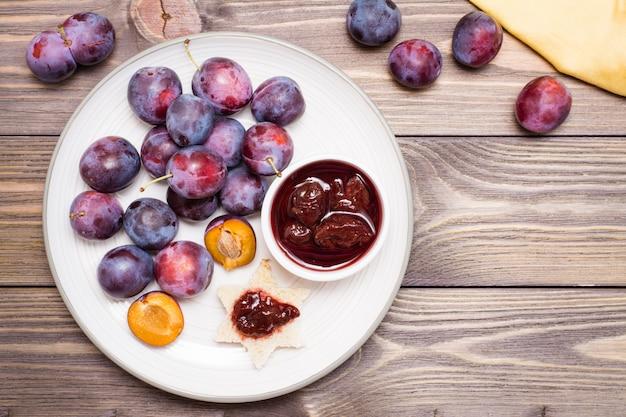 Bruschetta com geléia de ameixa e madura ameixa azul num prato na tabela de madeira vista superior