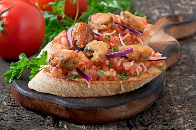 Bruschetta com mexilhões, queijo e tomate