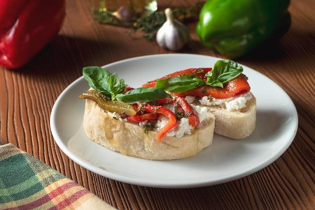 Bruschetta com pimentão, manjericão, molho pesto e mussarela em um prato branco sobre um fundo de madeira.