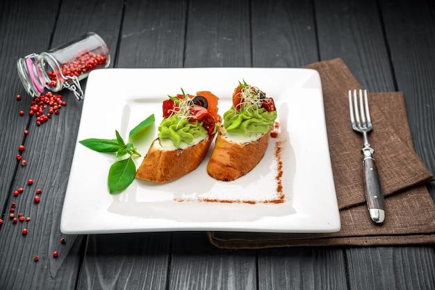 Bruschetta com presunto, abacate, tomate, rúcula e queijo parmesão