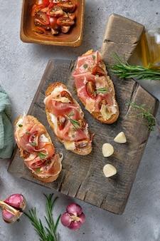 Bruschetta com presunto, queijo duro, tomate, ervas e especiarias em uma placa de madeira
