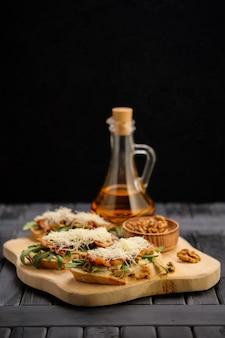 Bruschetta com queijo, bacon frito, azeitonas picadas e tomate seco