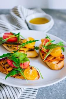 Bruschetta com salada de tomate cereja com queijo haloumi grelhado, com acelga e rúcula