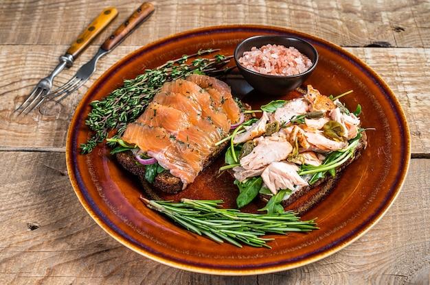 Bruschetta com salmão fumado quente e frio, rúcula, alcaparras num prato rústico com ervas. fundo de madeira. vista do topo.