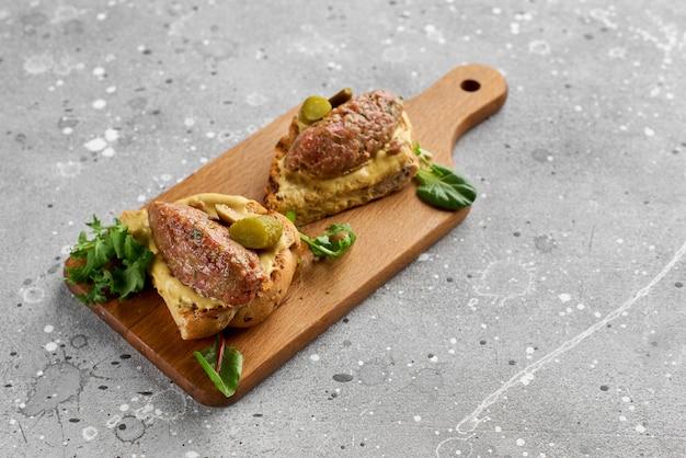 Bruschetta com tártaro de carne em uma placa de madeira. lanche saudável, saboroso e nutritivo
