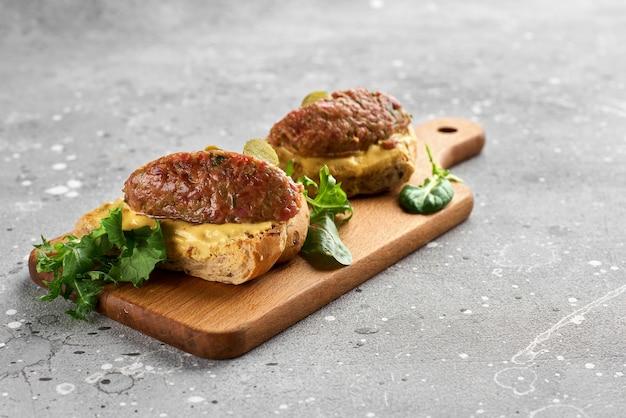 Bruschetta com tártaro de carne em uma tábua de madeira