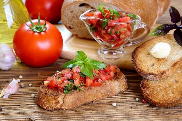 Bruschetta com tomate, alho e manjericão em uma mesa de madeira