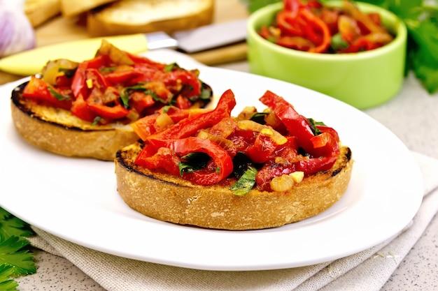 Bruschetta com tomate assado, pimentão, alho, cebola e salsa em um prato branco sobre um guardanapo sobre uma mesa de granito de fundo