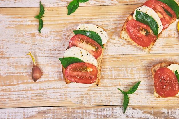 Bruschetta com tomate, queijo mussarela e manjericão