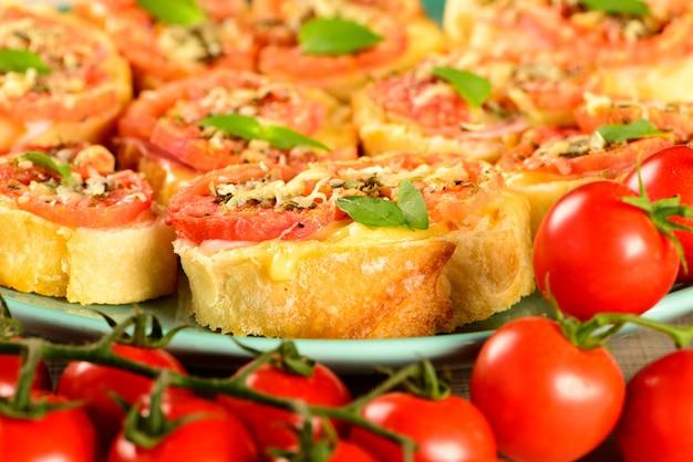 Bruschetta com tomate, queijo parmesão, azeite, presunto e orégano