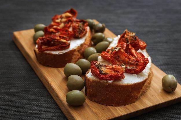 Bruschetta com tomate seco e queijo com azeitonas verdes em tábua de madeira cozinha mediterrânea