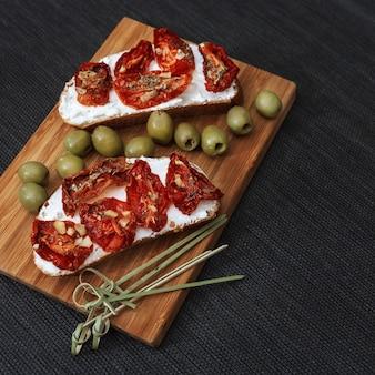 Bruschetta com tomate seco e queijo, com azeitonas verdes em uma placa de madeira.