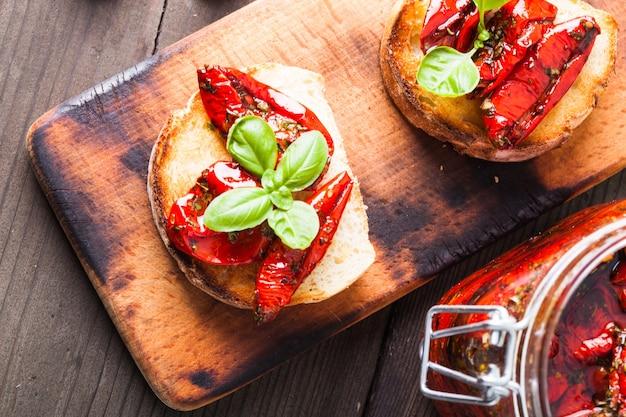 Bruschetta com tomates secos ao sol, folhas de manjericão e alho