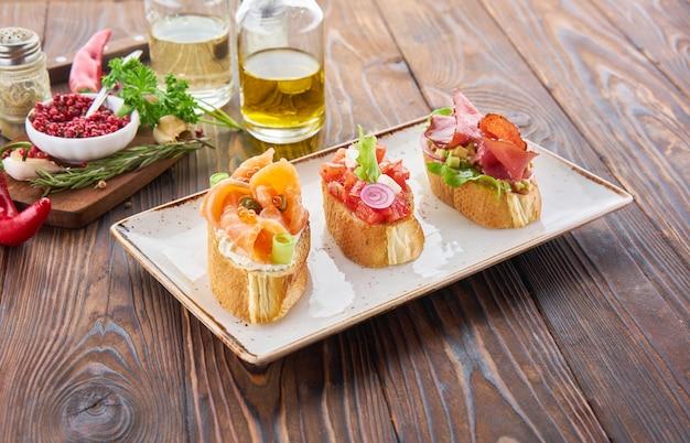 Bruschetta com várias coberturas, uma variedade de pequenos sanduíches com salmão peixe vermelho, legumes frescos, tomates e ervas na mesa de madeira
