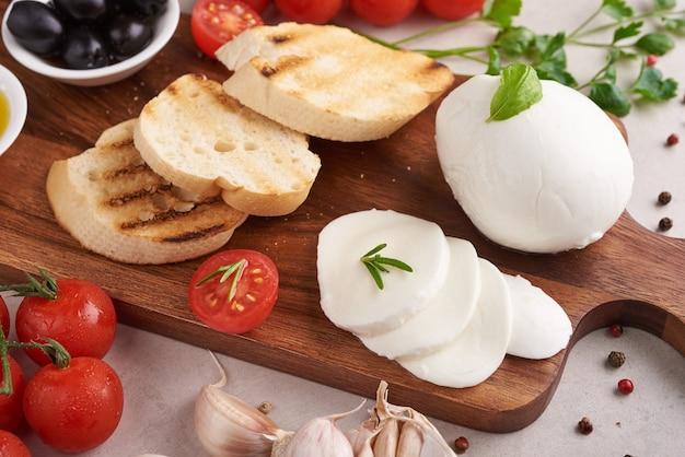 Bruschetta fresca com tomate, queijo mussarela e manjericão em uma placa de corte. aperitivo ou petisco italiano tradicional, antepasto. vista do topo. postura plana. ciabatta com tomate cereja.