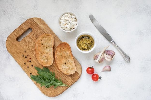 Bruschetta italiana com tomate assado, queijo mussarela e ervas sobre uma tábua.