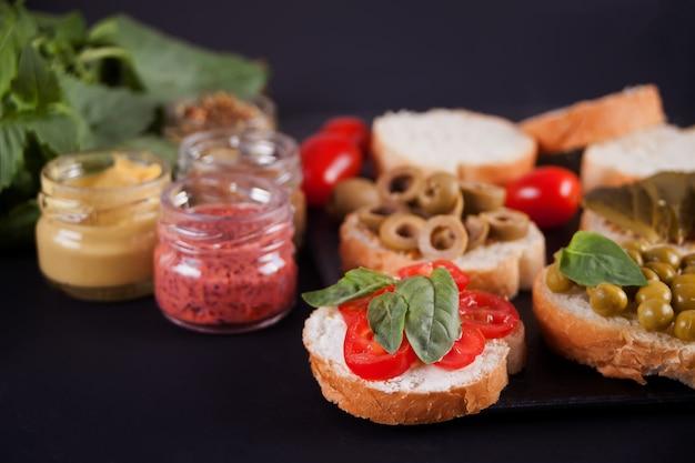 Bruschetta italiana no sortimento na placa, conjunto com pequena garrafa de mostarda