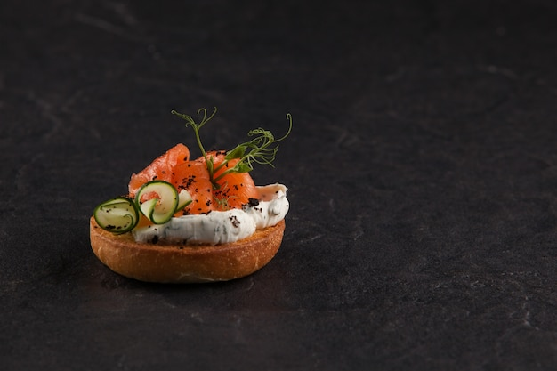 Bruschetta italiana redonda com peixe, tomate, cream cheese e vegetais.