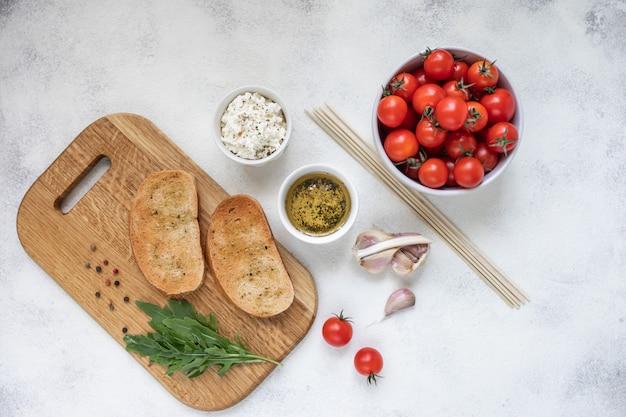 Bruschetta italiano com tomates roasted, mozzarella e ervas em uma placa de corte.