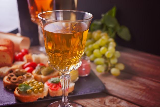 Bruschetta italiano na variedade na placa, vidros com vinho branco, uvas.