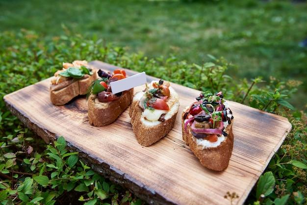 Bruschetta para vinho. variedade de pequenos sanduíches com presunto, tomate, queijo parmesão, manjericão fresco e creme balsâmico, servido na tábua de madeira rústica