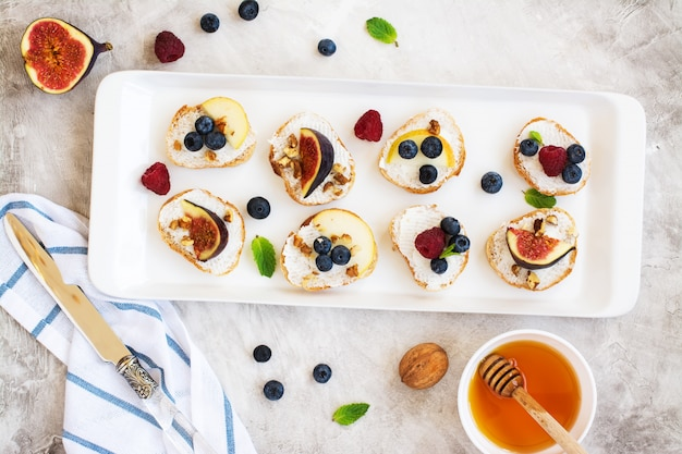 Bruschetta pequena com frutas, mel, ricota e hortelã