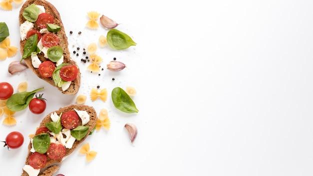 Bruschetta saborosa; macarrão farfalle cru e ingredientes frescos isolados sobre fundo branco