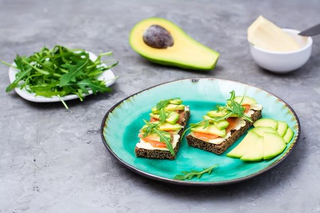 Bruschetta saboroso com salmão, manteiga, abacate e rúcula em um prato