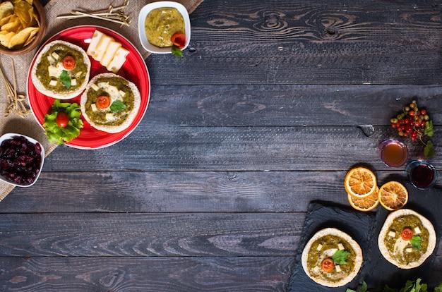 Bruschetta saboroso e delicioso com abacate e batatas fritas em uma mesa de madeira
