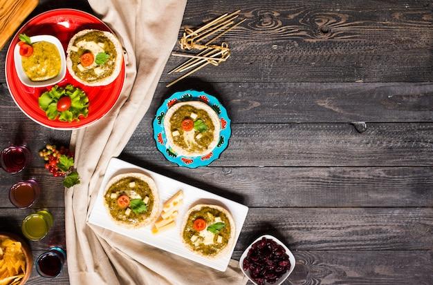 Bruschetta saboroso e delicioso com abacate, tomate, queijo, ervas, batatas fritas e licor, sobre um fundo de madeira.