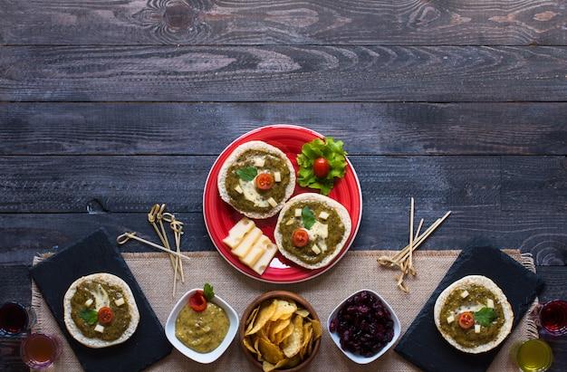 Bruschetta saboroso e delicioso com abacate, tomate, queijo, ervas, batatas fritas e licor.